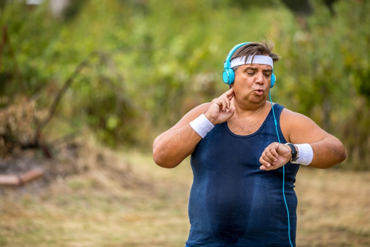 mature man checking his heart rate when exercising